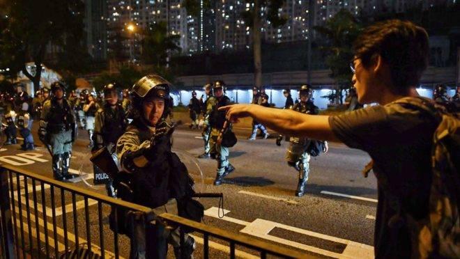 Manifestante e policial em confronto