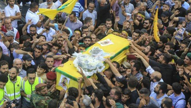 Members of Lebanon's Shiite Hezbollah movement carry the coffin of the fellow comrade, who was killed in Israeli strikes in Syria, during the funeral in the Ghobeiry neighbourhood of southern Beirut on August 26, 2019. – The head of Hezbollah Hassan Nasrallah said on August 25 that Israeli strikes overnight in Syria had hit a position used by his Lebanese Shiite group, killing two of its members. (Photo by – / AFP)