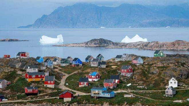 A picture taken on August 19, 2019 shows icebergs floating near the coast behind colourful houses in Kulusuk (aslo spelled Qulusuk), a settlement in the Sermersooq municipality located on the island of the same name on the southeastern shore of Greenland. (Photo by Jonathan NACKSTRAND / AFP)