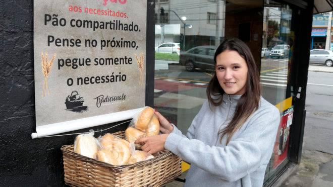 Luiza Adriano da Tradicionale Café & Panificadora que põe uma cesta com pães e salgados para doação do lado de fora do estabelecimento.