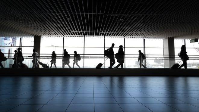 Passageiros transportando bagagens em aeroporto