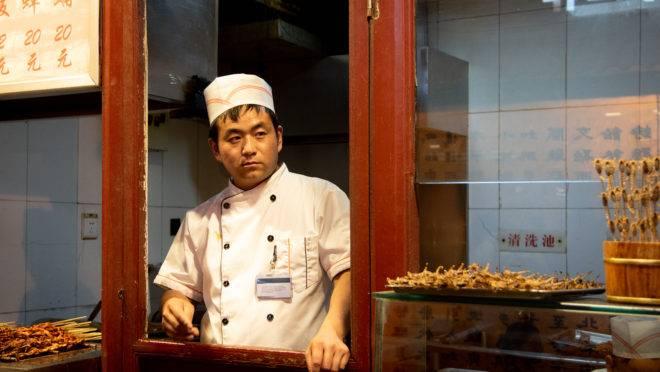 Chef chinês prepara alimentos típicos em mercado livre de Pequim