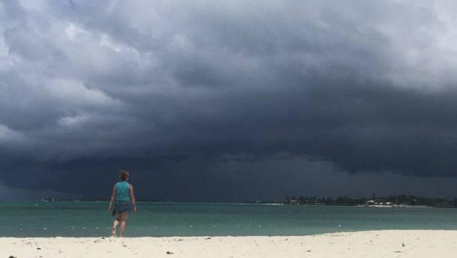 Mulher caminha pela praia enquanto uma tempestade se aproxima de Nassau, nas Bahamas, 12 de setembro de 2019