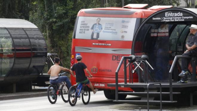 Cena comum na canaleta do biarticulado de Curitiba: jovens pegando rabeira no ônibus.