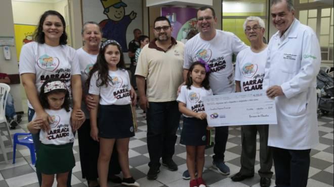 Manuela, que tratou um câncer no rim no Pequeno Príncipe, entrega cheque de R$ 16,2 mil ao diretor do hospital, Donizetti Giamberardino Filho.