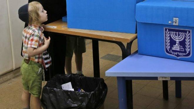 Criança observa homem preencher cédula durante a eleição parlamentar de Israel em Tel Aviv, 17 de setembro de 2019