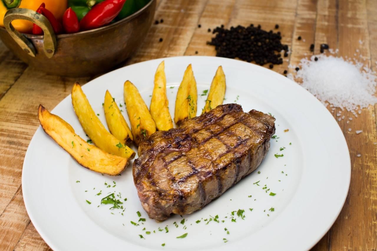 Bife de chorizo Black Angus com batatas rústicas, da Devons, o prato principal da Noite em Buenos Aires.