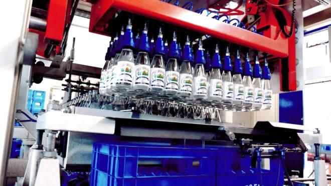 Garrafas de água ouro fino sendo envasadas automaticamente, na linha de produção.