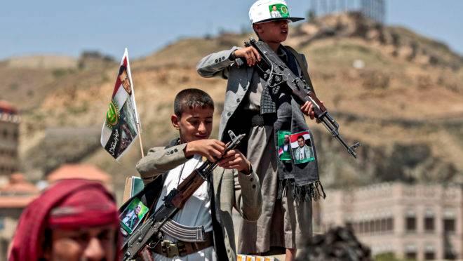 Garotos iemenitas seguram armas que lhes foram dadas pelos rebeldes houthis, no Iêmen