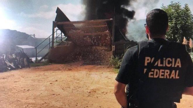 Policial federal observa incineração de drogas.