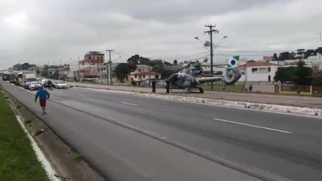 Helicóptero pousado em rodovia para socorrer vítima atropelada
