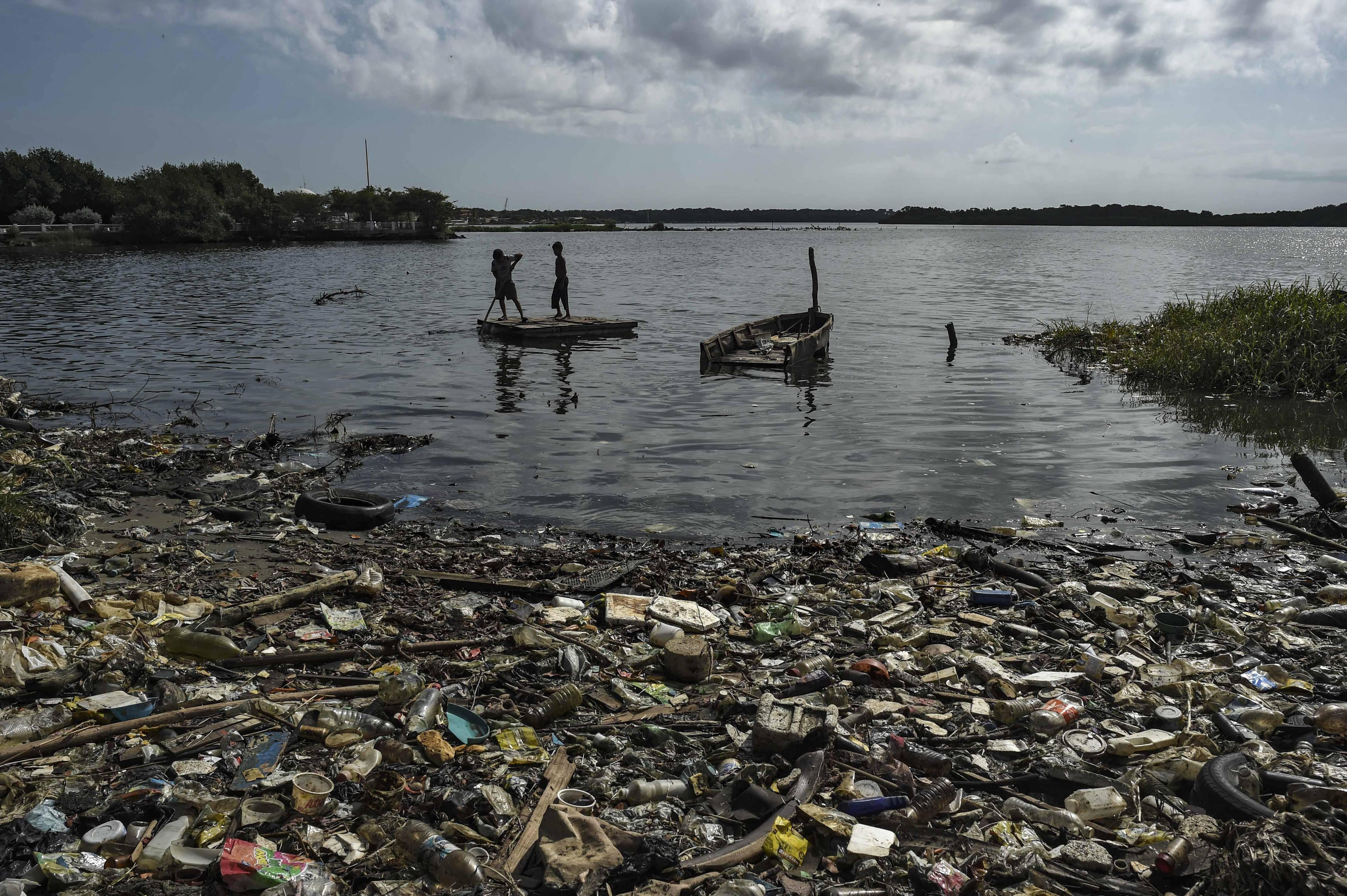Crianças navegam em uma pequena balsa nas águas poluídas do lago Maracaibo | Foto: YURI CORTEZ / AFP