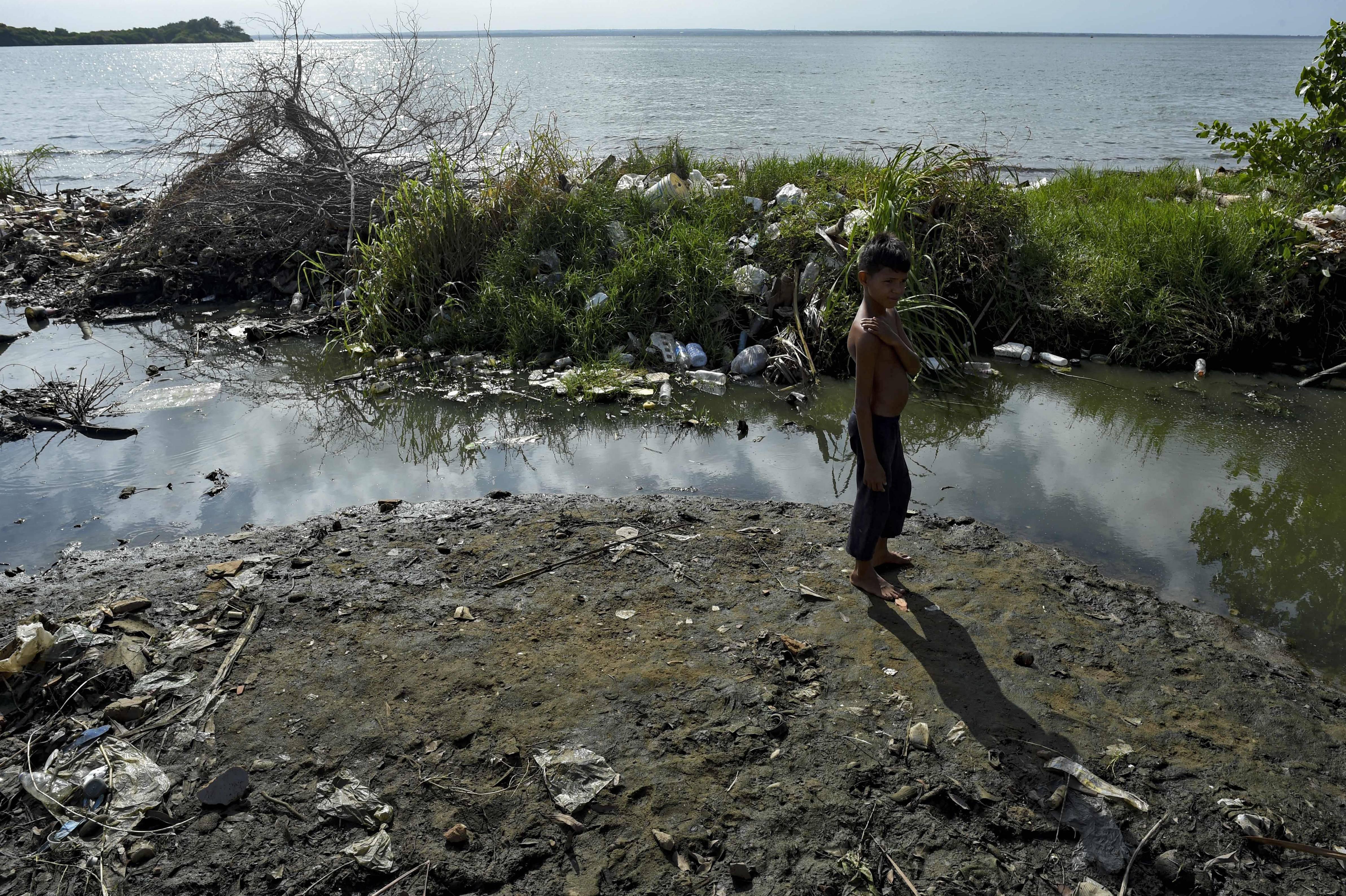 Criança às margens do poluído lago Maracaibo | Foto: YURI CORTEZ/AFP