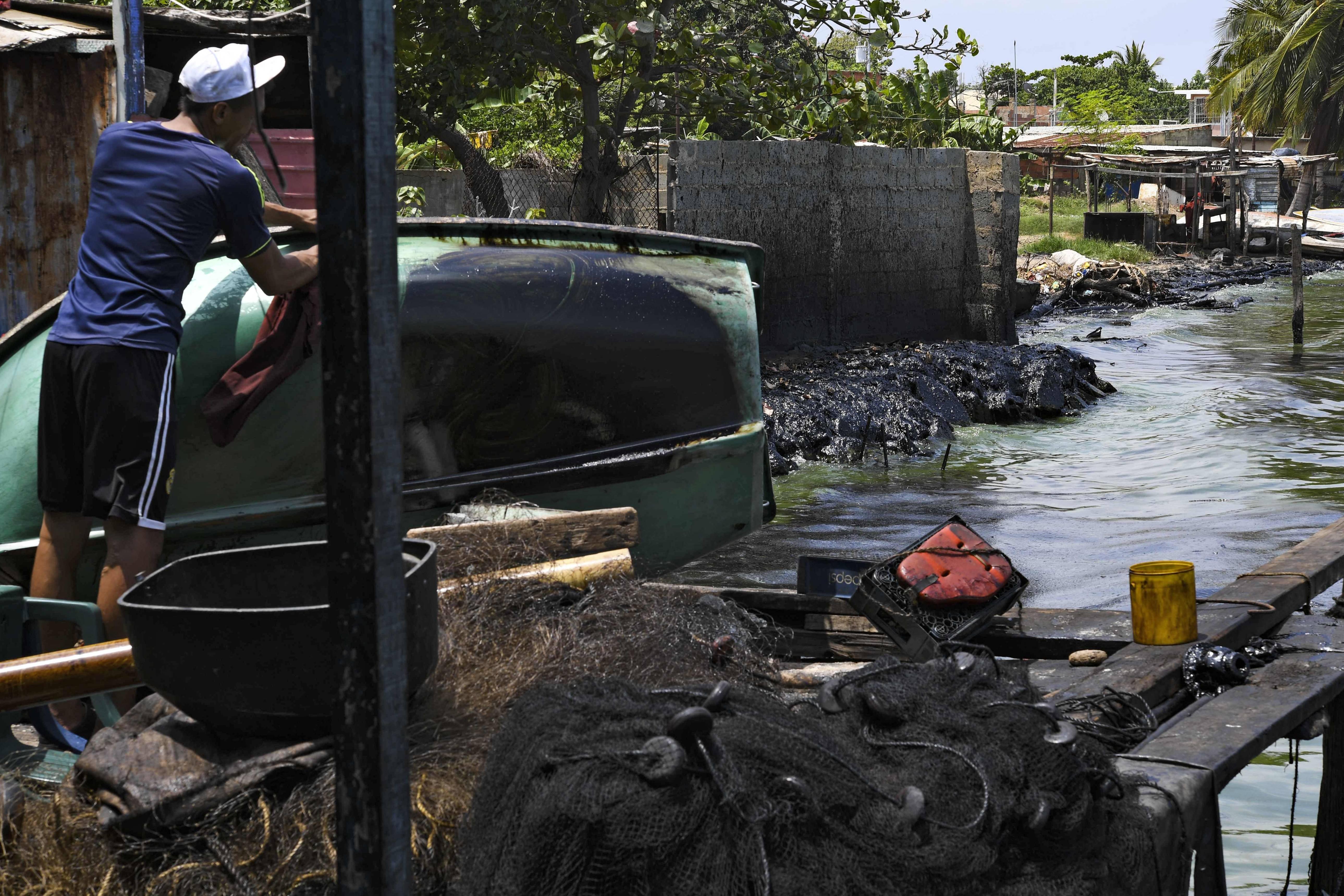 Um pescador limpa o óleo de seu barco, nas margens do poluído lago Maracaibo | Foto: YURI CORTEZ / AFP