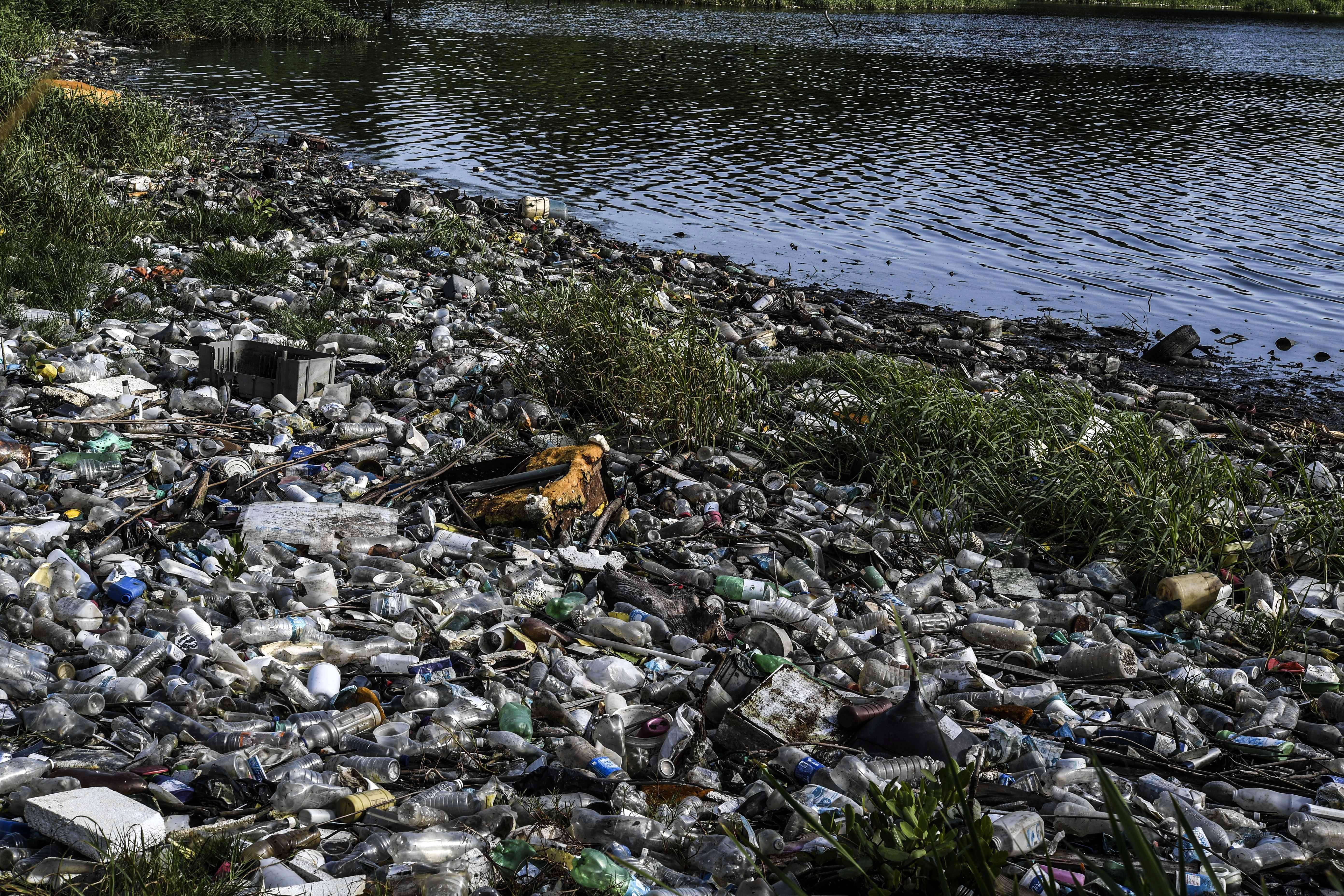 Lixo nas margens do poluído lago Maracaibo | Foto: YURI CORTEZ / AFP