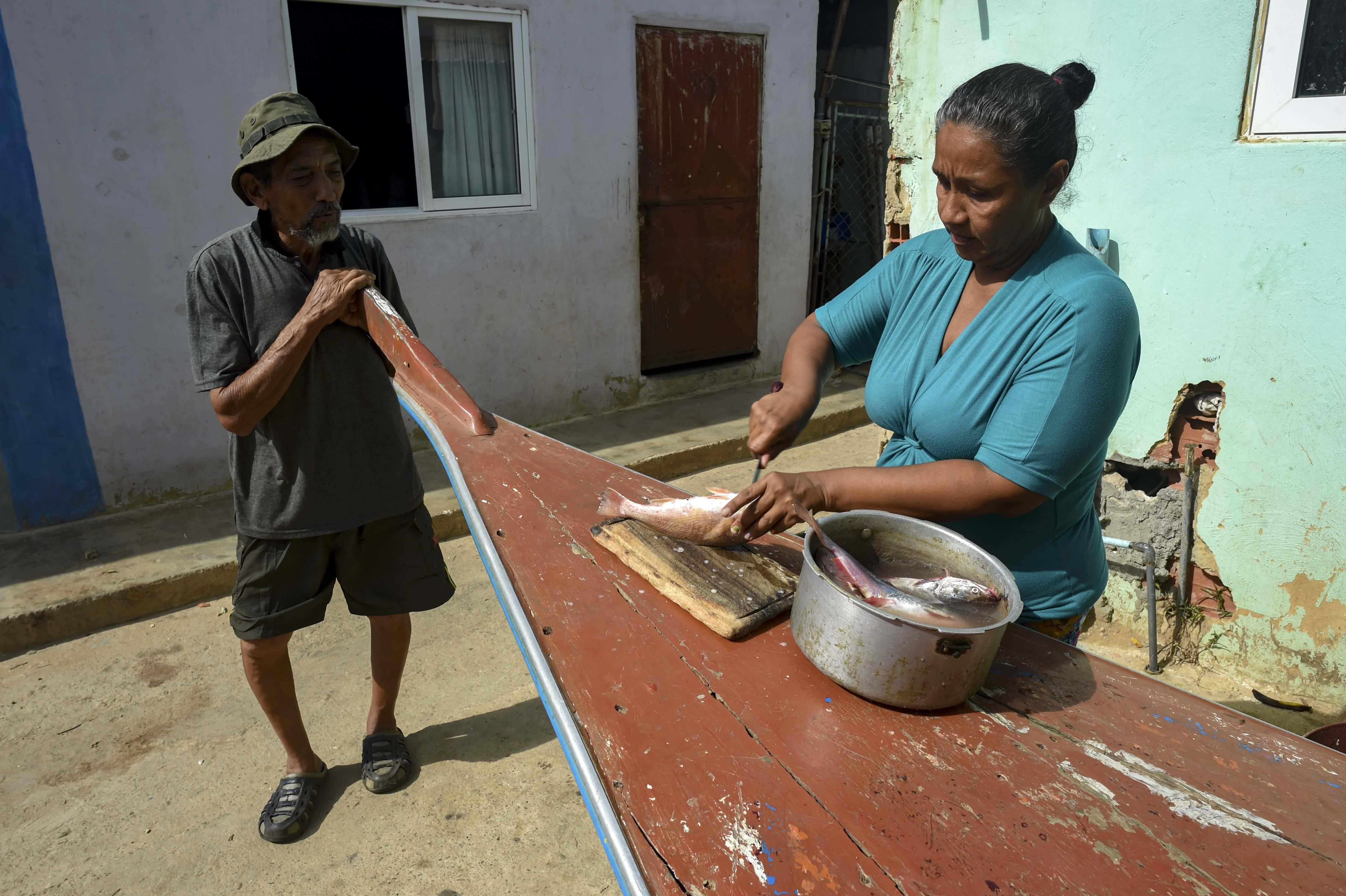 Uma mulher limpa um peixe extraído do poluído Lago Maracaibo | Foto: YURI CORTEZ / AFP