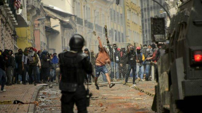 Demonstrators clash with riot police in downtown Quito during a transport strike against the economic policies of the government of Ecuadorean President Lenin Moreno regarding the agreement signed on March with the International Monetary Fund (IMF), on October 3, 2019. – The Ecuadorean government confirmed possible labour and tax reforms as established in the agreement, Economy Minister Richard Martinez stated -a day after announcing the elimination of fuel subsidies. (Photo by Rodrigo BUENDIA / AFP)