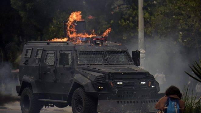Veículo da polícia em chamas durante protestos contra políticas econômicas do governo do presidente do Equador Lenín Moreno, em Quito, 4 de outubro de 2019