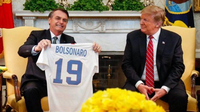 Bolsonaro exibe camisa da seleção dos EUA com seu nome durante encontro com Trump na Casa Branca, em março deste ano: relações sofrem abalo.