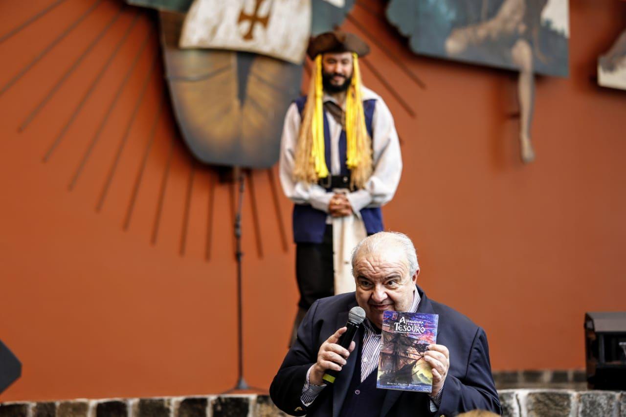 O prefeito Rafael Greca mostra o livro às crianças no Memorial de Curitiba.
