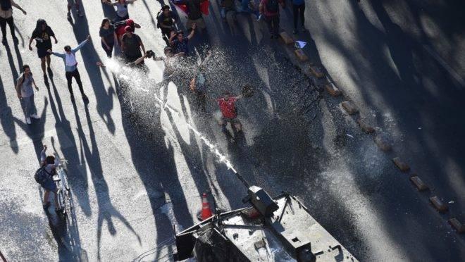 Polícia de choque dispersa manifestantes com canhão de água no centro de Santiago, Chile, 21 de outubro de 2019