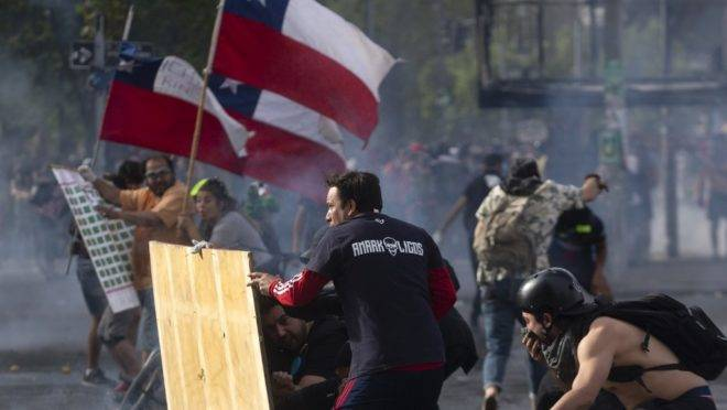 Demonstrators clash with riot police on the fifth straight day of street violence which erupted over a now suspended hike in metro ticket prices, in Santiago, on October 22, 2019. – President Sebastian Pinera held a meeting with leaders of some of Chile's opposition parties on Tuesday, aiming to find a way to end street violence that has claimed 15 lives amid sustained protests. (Photo by CLAUDIO REYES / AFP)