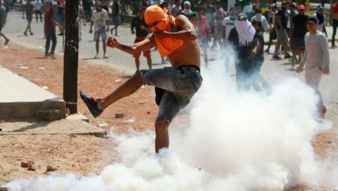 Apoiador do partido de Carlos Mesa, principal adversário de Evo Morales na eleição presidencial, chuta uma bomba de gás lacrimogêneo em confronto entre partidários dos dois candidatos em meio à disputa sobre resultados, Santa Cruz, Bolívia, 23 de outubro de 2019