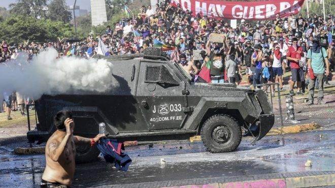 Manifestante atira pedra em veículo da polícia durante protestos em Santiago, Chile, 24 de outubro de 2019