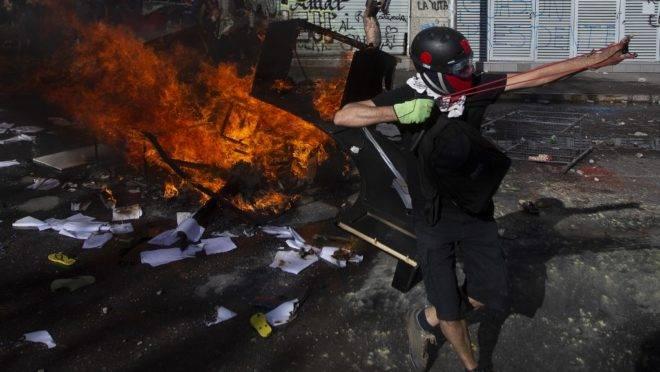 Confronto entre manifestantes e a polícia de choque em Santiago, Chile, 24 de outubro de 2019