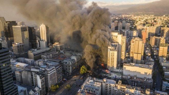 Fumaça sobe de um prédio em chamas perto do local onde manifestantes protestavam em Santiago, Chile, 28 de outubro de 2019