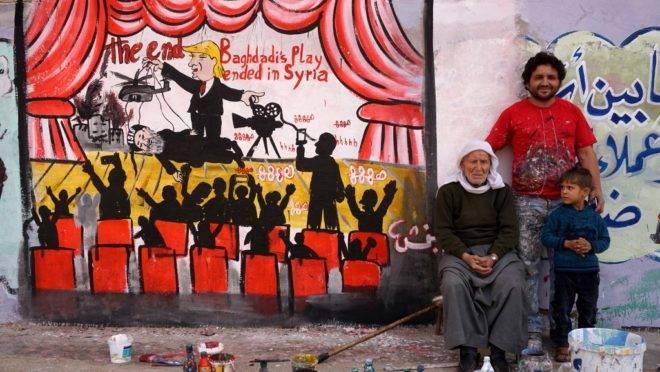 """Uma foto tirada em 28 de outubro de 2019 mostra o artista sírio Aziz al-Asmar (C) posando com parentes perto de um mural que ele pintou na cidade de Binnish, no noroeste da província de Idlib, representando o presidente dos EUA, Donald Trump, dirigindo uma """"peça"""" com a morte Abu Bakr al-Baghdadi, líder do grupo Estado Islâmico (IS), na Síria."""