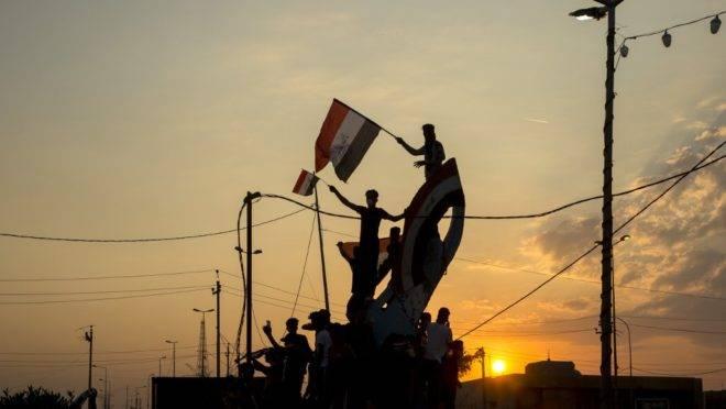 Manifestantes iraquianos agitam bandeiras do seu país em frente à sede do governo na cidade de Basra durante protestos contra o governo, 30 de outubro de 2019