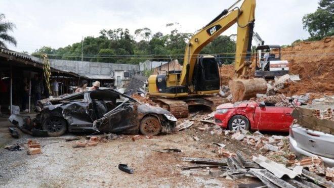 Carros ficaram soterrados sete meses debaixo do muro que desabou durante chuva.