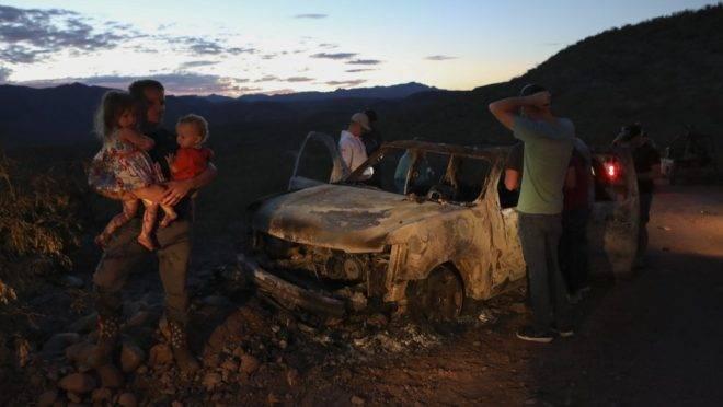 Membros da família LeBarón olham para o carro queimado onde alguns dos nove familiares foram mortos em emboscada em Sonora, México, 5 de novembro de 2019