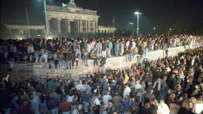 Milhares de cidadãos de Berlim Oriental se reúnem no Muro de Berlim, perto do Portão de Brandenburgo (ao fundo), após a queda do Muro, 10 de novembro de 1989