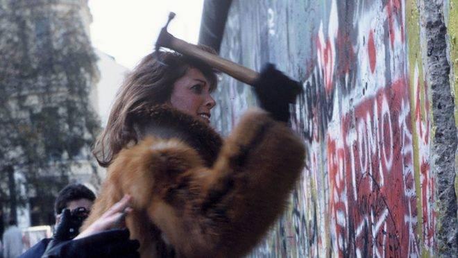 """Alemã tenta arrancar pedaços do Muro de Berlim, em novembro de 1989. Os cidadãos que usaram marretas e outras ferramentas para derrubar o muro aos poucos ficaram conhecidos como """"Mauerspechte"""" (pica-paus de muro)."""