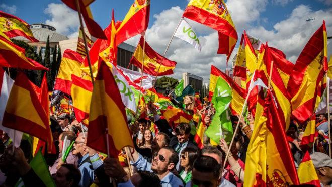 Apoiadores agitam bandeiras espanholas e do partido Vox em comício do Vox em Barcelona, Espanha, 30 de março de 2019