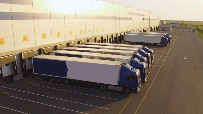 Caminhões estacionados em frente a um depósito aguardando carregamento