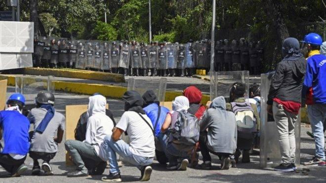 Estudantes universitários se protegem durante enfrentamento com a Polícia e a Guarda Bolivariana na entrada da Universidad Central de Venezuela, em Caracas, 14 de novembro de 2019