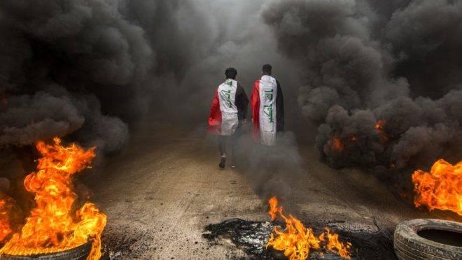 Manifestantes caminham por nuvens de fumaça de pneus queimados na cidade de Basra, sul do Iraque, 17 de novembro de 2019