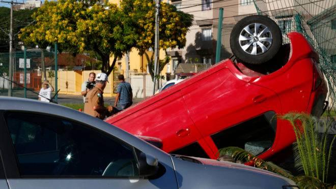 Carro capota após acidente.