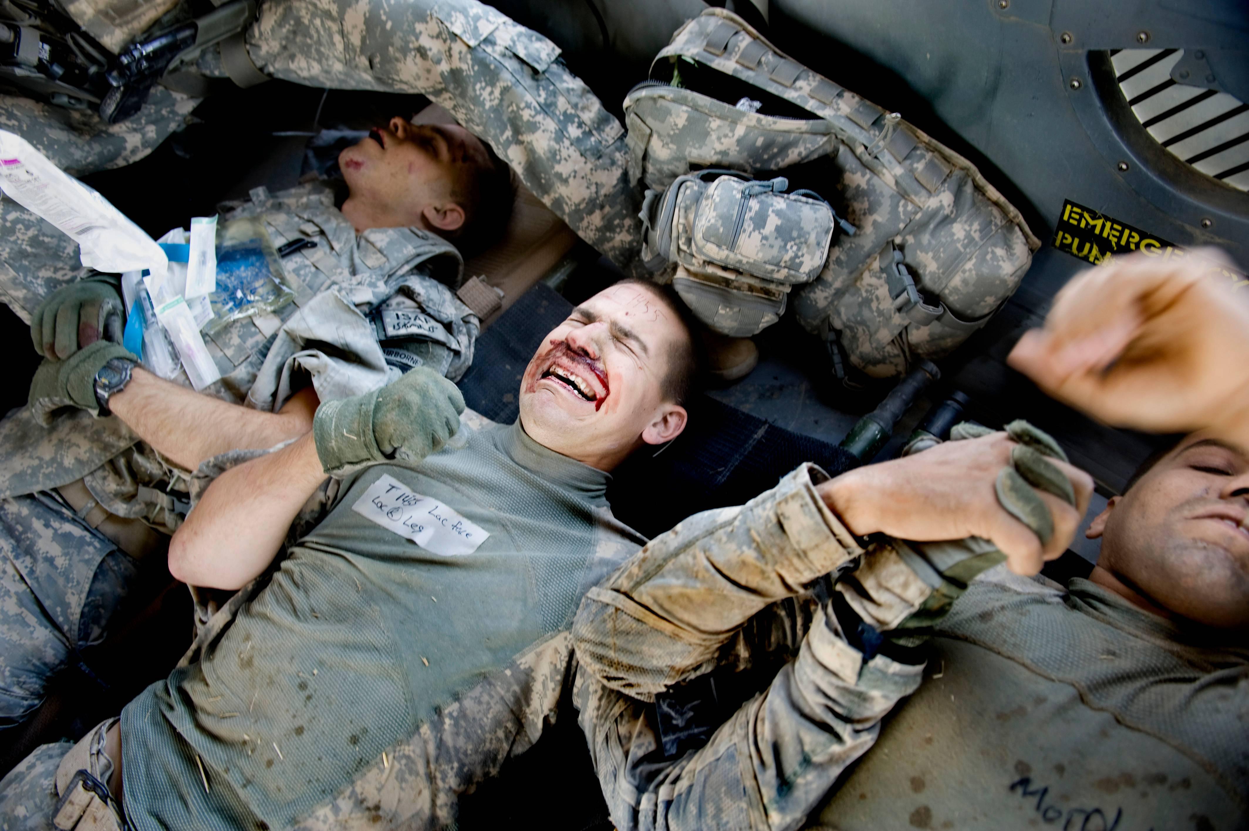 O soldado Terry Heise grita de dor enquanto os médicos da Força-Tarefa Shadow cuidam de um ferimento em sua perna após um acidente de carro na província de Kandahar, Afeganistão, em 10 de outubro de 2010. O PFC do exército Jeff Springer, à esquerda, e o sargento Rodrigo Santos são transportados com Heise depois que um IED explodiu sob seu veículo, matando outros dois soldados. Os três sobreviveram, mas com ferimentos nas extremidades inferiores; um perdeu um pé | Foto: Washington Post/Linda Davidson