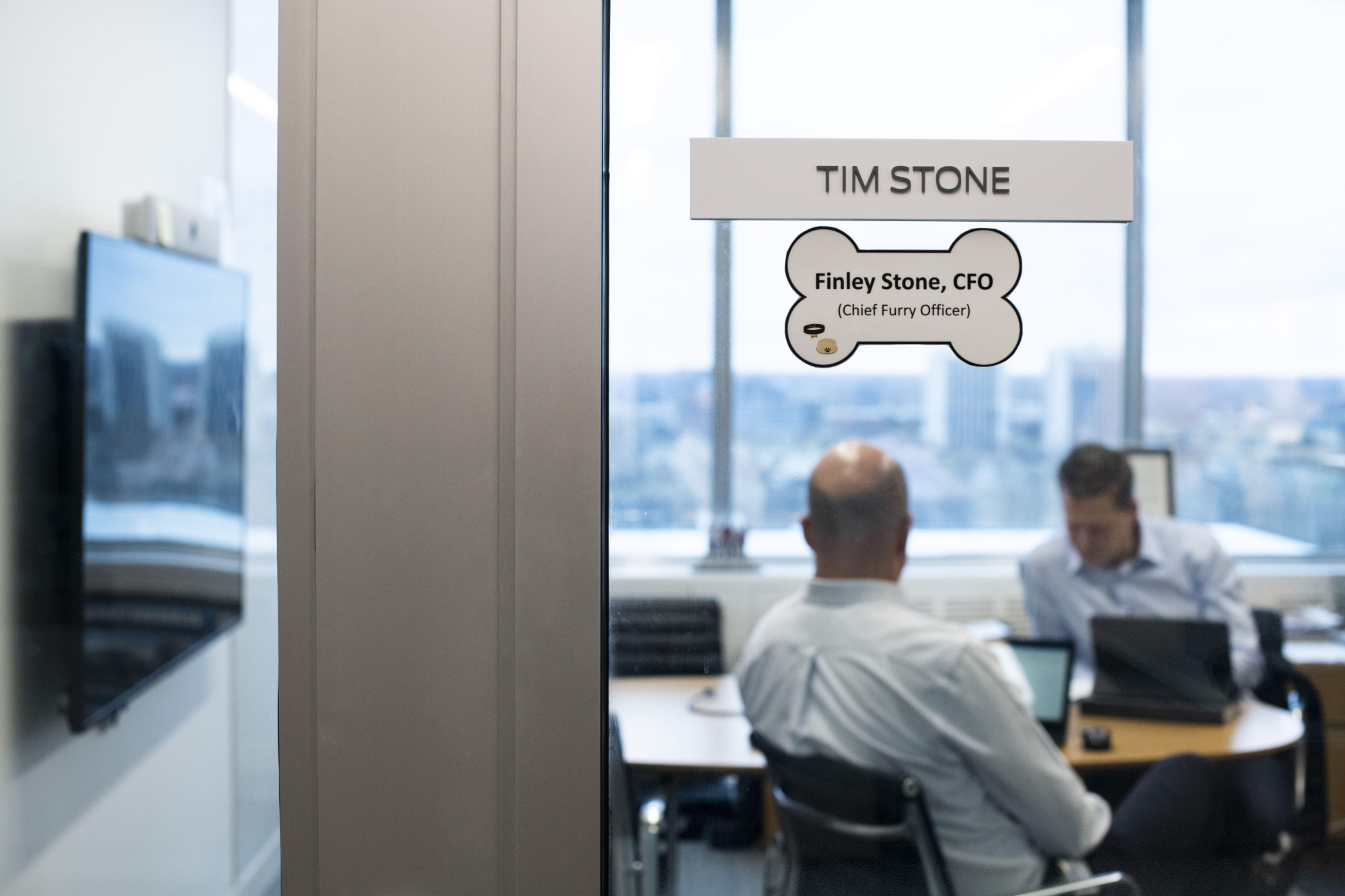 """Dois títulos, a mesma sigla: o chief finance officer Tim e o chief furry officer Finley """"dividem"""" o escritório. Crédito: Brittany Greeson/ Bloomberg."""