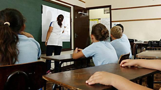 Professora e alunos em sala de aula em escola municipal.