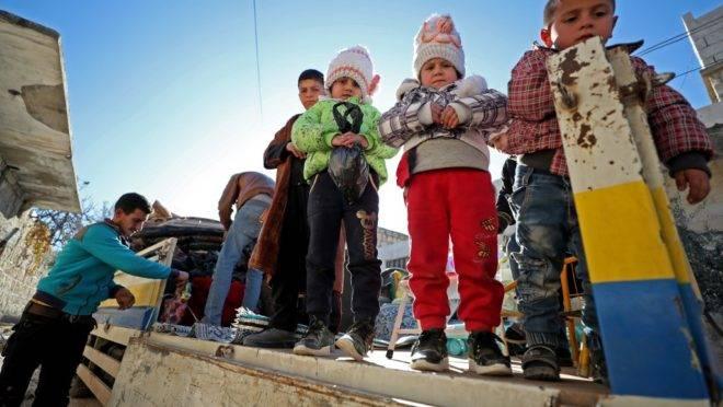 Família deixa a cidade controlada por jihadistas Maaret al-Numan, em Idlib, Síria, que estava sendo bombardeada, 20 de dezembro. Dezenas de milhares de civis estão fugindo de bombardeios em Idlib, agravando a situação humanitária