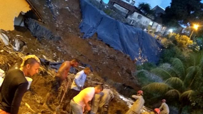 Pessoas trabalham no resgate de vítimas em área com casas destruídas.