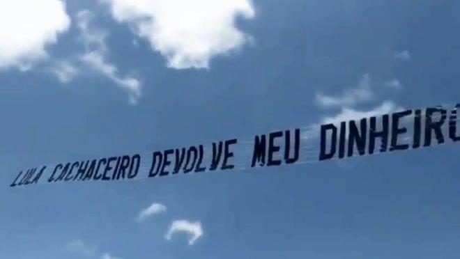 """Avião patrocinado pelo dono da Havan sobrevoa praia de Santa Catarina com faixa com a frase """"Lula cachaceiro devolve meu dinheiro""""."""