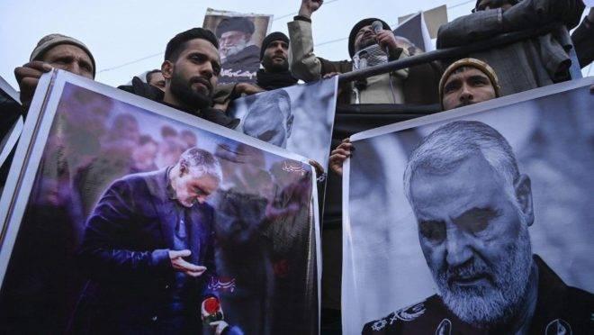 Manifestantes protestam contra os Estados Unidos, com fotos do general morto Qasem Soleimani.