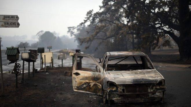 Um veículo queimado é visto na rua Quinlans
