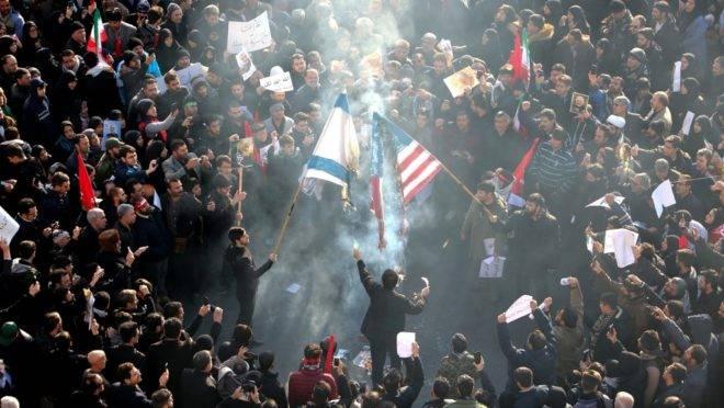 Iranianos queimam bandeiras dos EUA e de Israel durante procissão em homenagem ao general Qasem Suleimani em Teerã, 6 de janeiro de 2020